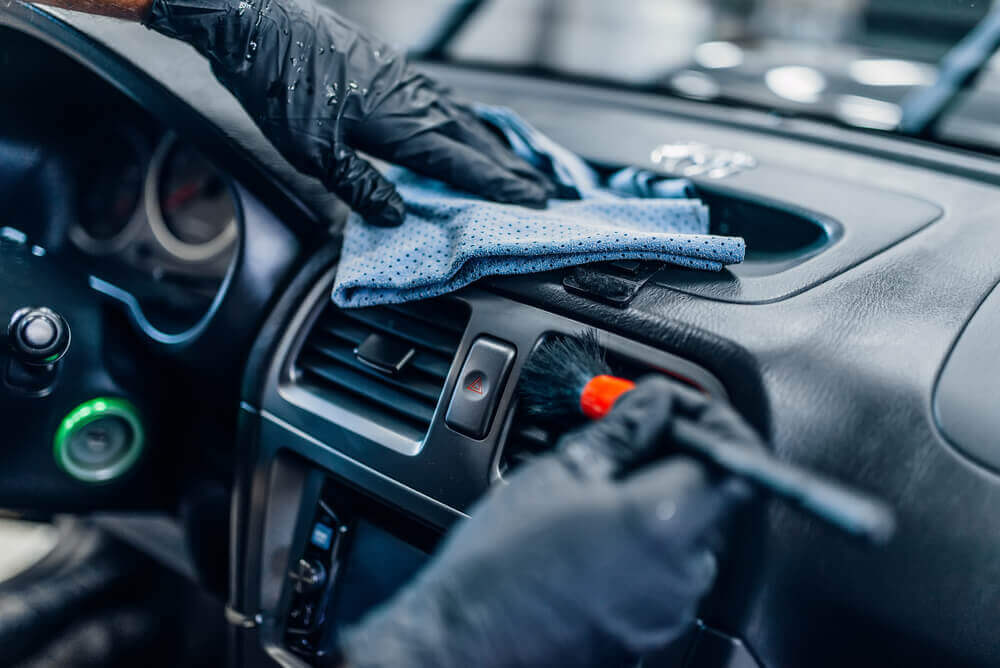 close up image of a cleaner wearing black gloves cleaning the air vents of a car interior