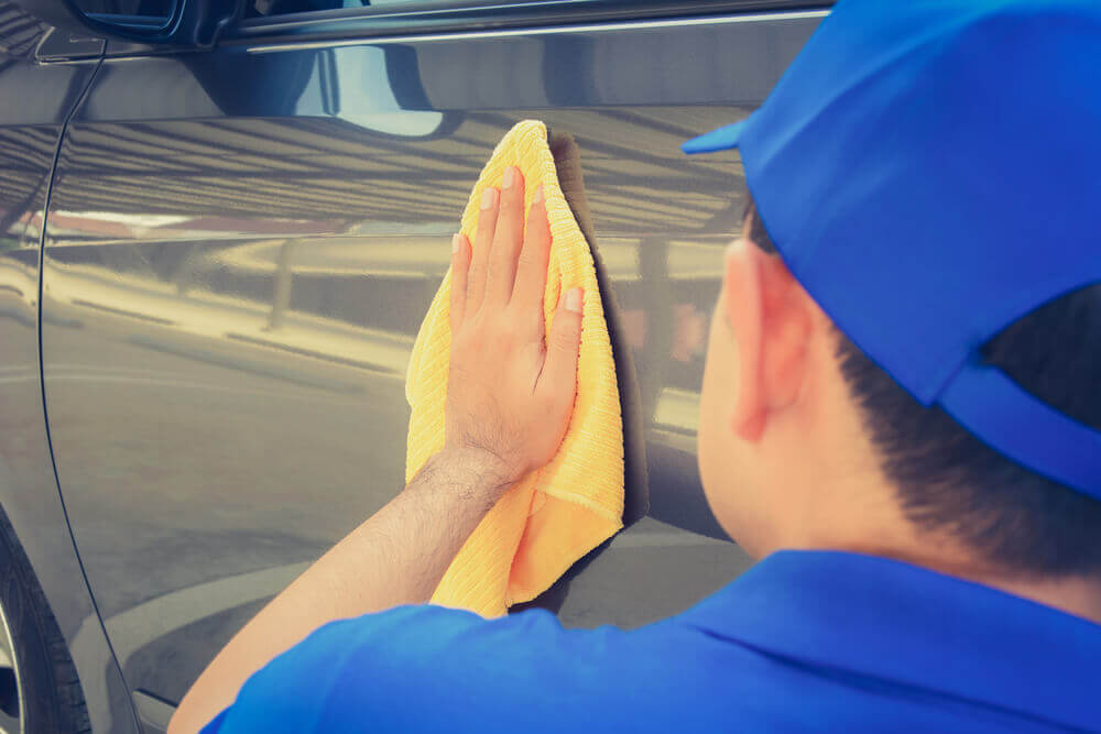 view from behind the head of a worker wiping down the side of a car with a cloth