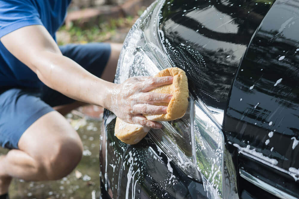 outside image of a cleaner washing the headlight of a car with a sponge and soapy water