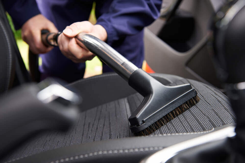 image of the seat of a car with somebody vacuuming the seat