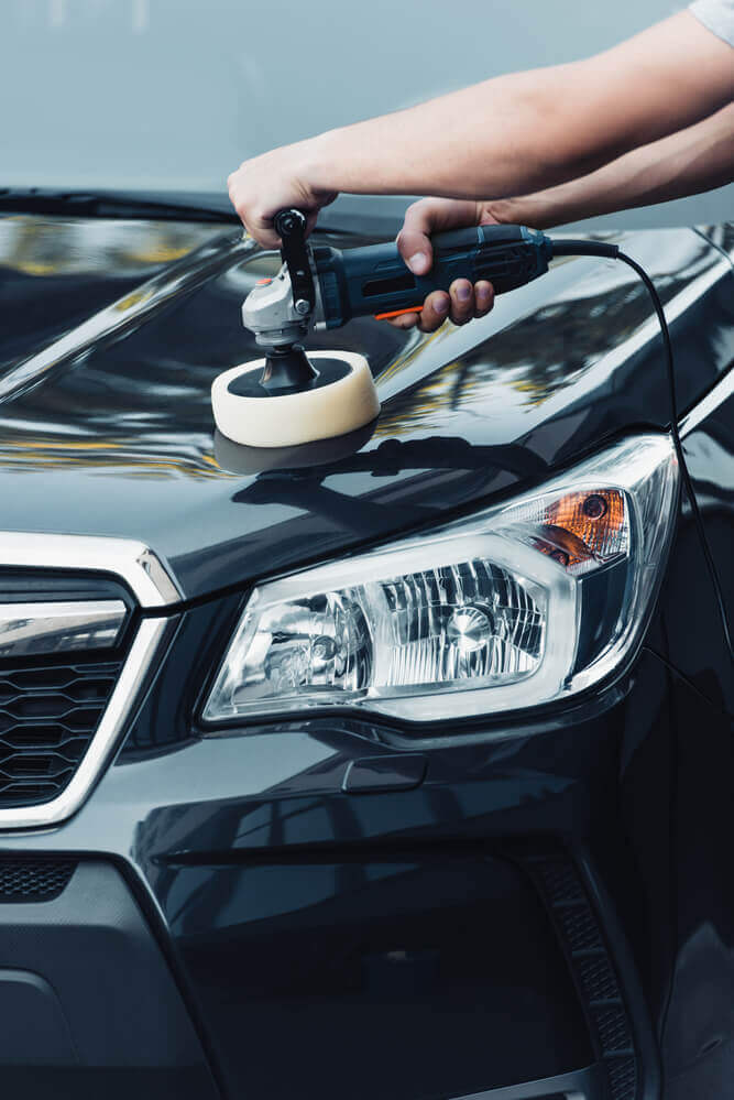front view of a cleaner using a buffing machine on the bonnet of a black car