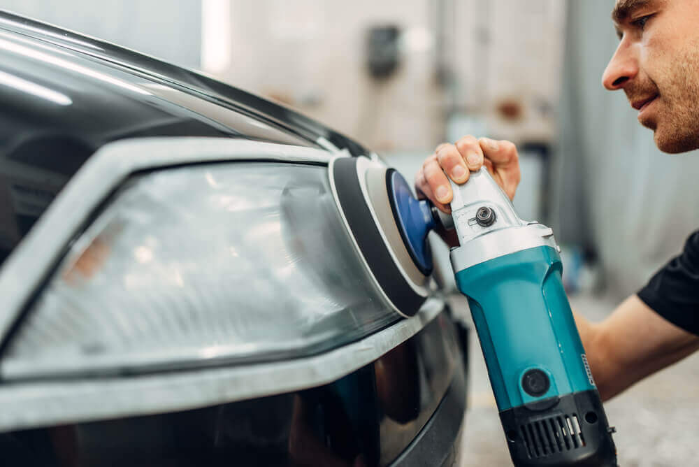 close up of a worker using a buffing machine on the headlight of a car