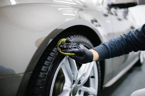 close up of a worker cleaning the rim of a car