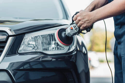 front shot of a cleaner buffing the headlight of a car with protective tape surrounding the headlight